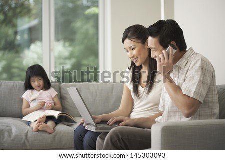 Daughter watching couple use laptop and cellphone on sofa at home - stock photo