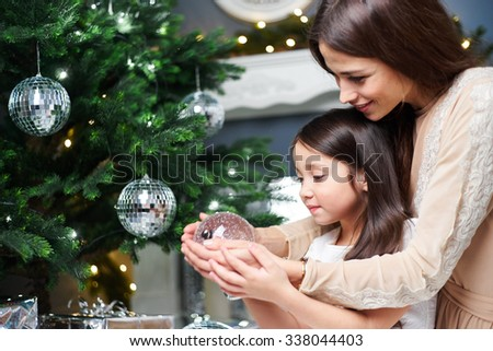Daughter with her mother decorate the Christmas tree.  - stock photo