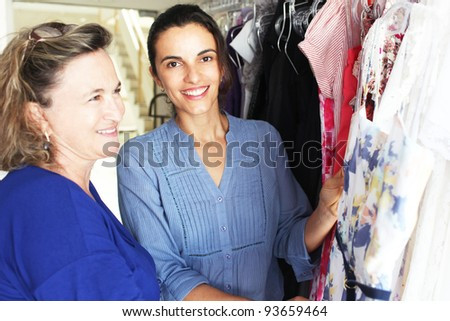Daughter with mother buying clothes - stock photo