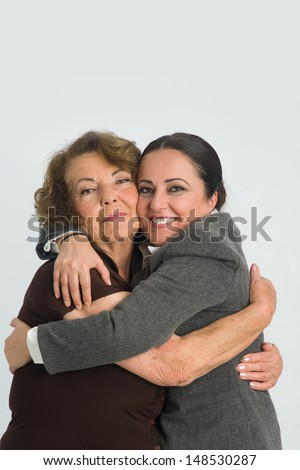 Daugter is hugging her mother with happy expression on her face. - stock photo