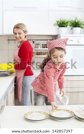 Dauhter helping her mother with dishwashing in the kitchen - stock photo