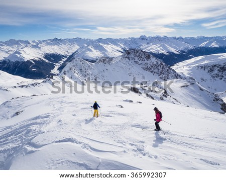 DAVOS, SWITZERLAND - JANUARY 12, A couple of skiers skiing downhil course in the Parsenn mountains, Davos, Switzerland, 2015 - stock photo