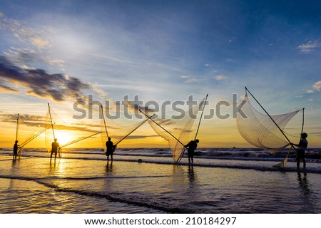 Dawn at Hai Thinh beach, Namdinh, Vietnam. Fishermen fishing in the sea at sunrise. They use a small net to scoop the seafood near the beach.. - stock photo