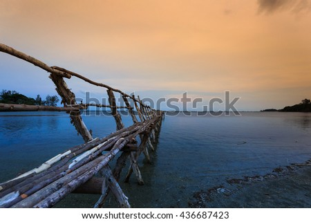 dawn by the beach with wooden jetty. the majestic sunrise at the beach with the jetty as point of interest. long exposure cause the motion of the water and clouds. - stock photo