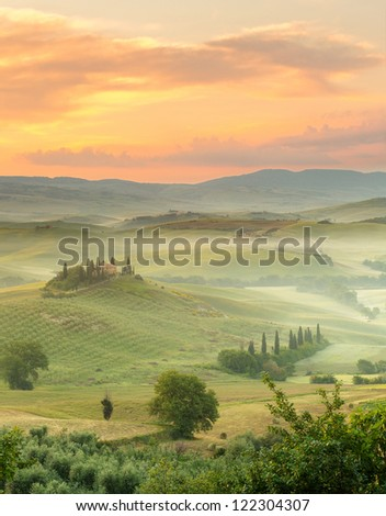 Dawn in a misty valley in the hills near Pienza, Tuscany, Italy - stock photo