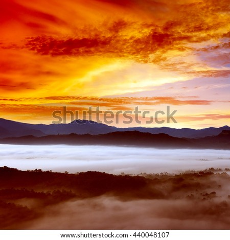 Dawn in mountains covered mist. Bright orange sky. - stock photo