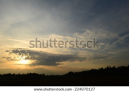 Dawn in the clouds on a blue sky sunlight falls on the forest and swamp - stock photo