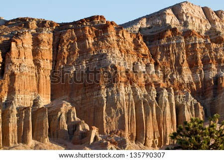 Dawn lights a rock wall at Red Rock Canyon State Park and Red Cliffs Nature Preserve in California's Mohave Desert - stock photo