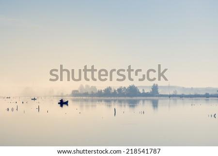 Dawn on lake. Focus on fisherman. - stock photo