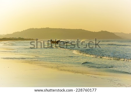 Dawn on the coast of Goa. Fishing boat on the waves ready to sail the high seas - stock photo