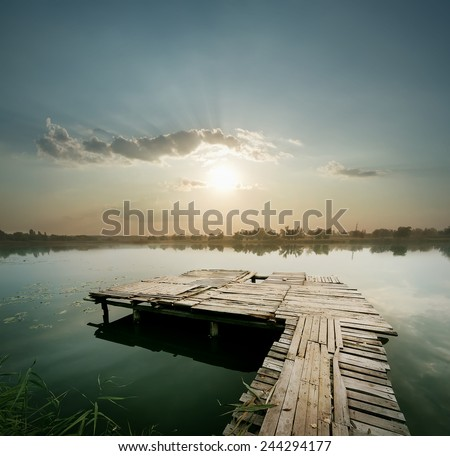 Dawn on the lake with pier under the blue cloudy sky - stock photo
