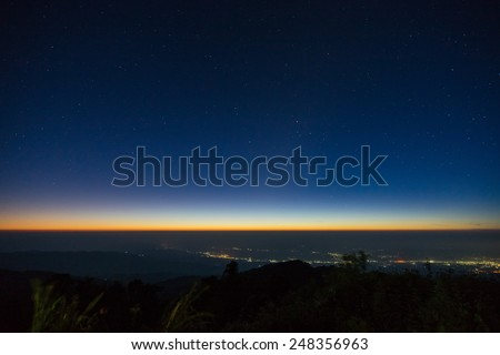 Dawn on the mountain The stars and the lights of the city. - stock photo