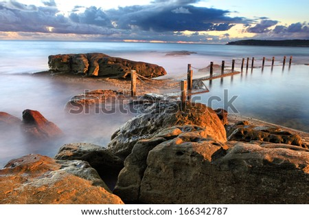 Dawn shot of the coastline of Maroubra and Mahon Pool.  There is a light that illuminates the pool at night which is interplaying with the natural light.   Long exposure bracketed with lens filter - stock photo