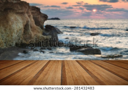 Dawn sunrise landscape over beautiful rocky coastline in Mediterranean Sea with wooden planks floor - stock photo