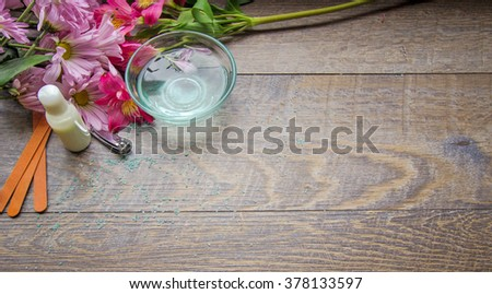 Day At The Spa. Fresh flowers with emery board, lotion, nail clippers and essential oils for manicure or pedicure. Shot from above with copy space. - stock photo
