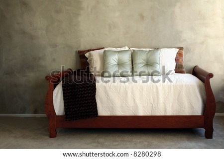 Day bed with cream linens against green textured wall - stock photo
