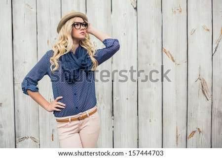 Day dreaming trendy model posing on wooden background - stock photo