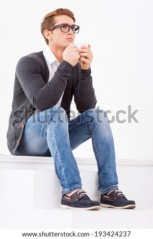 Day dreaming with cup of fresh coffee. Handsome young man drinking coffee and looking away while standing indoors - stock photo