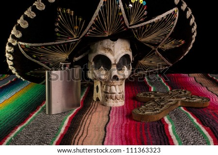 Day of The Dead (Dia de los Muertos) skull with with decorative cross, tequila flask on a traditional mexican blanket. - stock photo