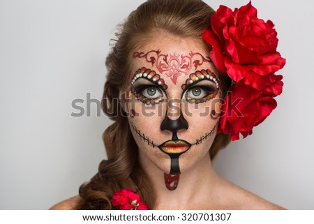 Day of the Dead, Skull Mask. Art woman beautiful face painted as a traditional day of the dead, red flowers on head. Free place on photo for congratulations. Good for Halloween card, present, banner - stock photo
