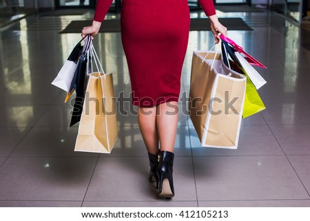 day shopping. Closeup beautiful legs of  business woman carrying shopping bags while walking along the 	