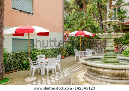 Day view of a hotel exterior with an old fountain. - stock photo