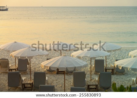 Daybeds and umbrella on the Beach at sunrise - stock photo