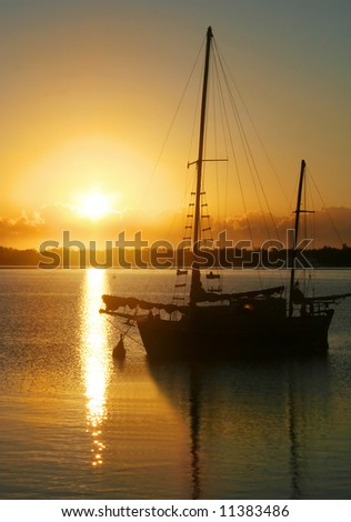 Daybreak through clouds over an old ketch. - stock photo