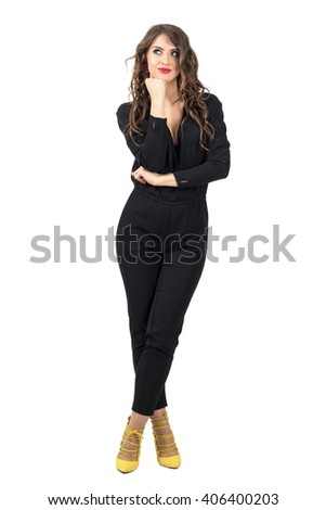 Daydreaming brunette beauty in black overalls looking up. Full body length portrait isolated over white studio background. - stock photo