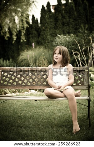 Daydreaming child portrait - little girl sitting on bench outdoor in backyard - stock photo