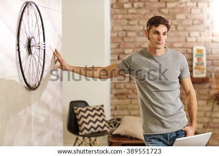 Daydreaming man leaning against wall at retro home, looking down. - stock photo