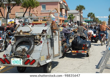 "DAYTONA BEACH, FL - MARCH 17:  A customized motorcycle towing a trailer cruises Main Street on St. Patrick's Day during ""Bike Week 2012"" in Daytona Beach, Florida. - stock photo"