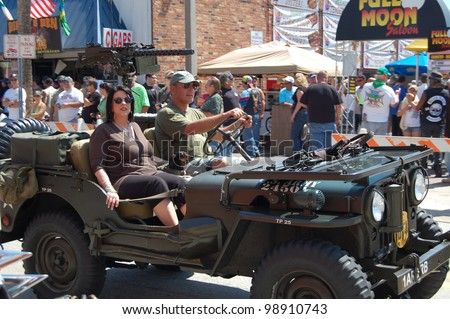 "DAYTONA BEACH, FL - MARCH 17:  An unidentified couple and their dog cruise down Main Street in a U.S. Army jeep during ""Bike Week 2012"" in Daytona Beach, Florida. - stock photo"