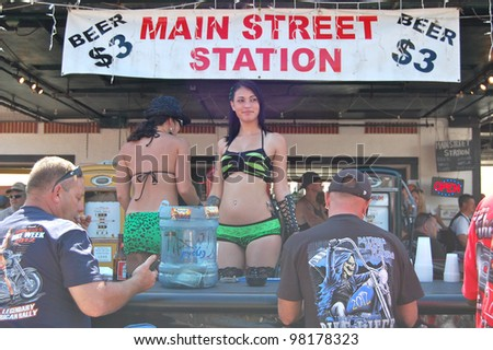 "DAYTONA BEACH, FL - MARCH 17:  Barmaids celebrate St. Patrick's Day on Main Street amid the sea of bikers in town for ""Bike Week 2012"" in Daytona Beach, Florida. March 17, 2012 - stock photo"