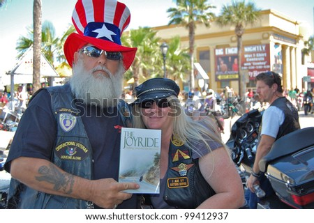 "DAYTONA BEACH, FL - MARCH 17:  Pastors Montana and Joy Mormur promote her book ""The JoyRide"" and their Church on Wheels ministry on Main Street during ""Bike Week 2012"" in Daytona Beach, Florida. - stock photo"