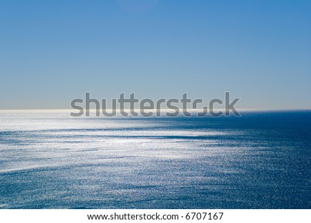 Dazzling silver reflections of light off the pacific ocean under a perfect blue sky. Plenty of space for Copyspace - stock photo