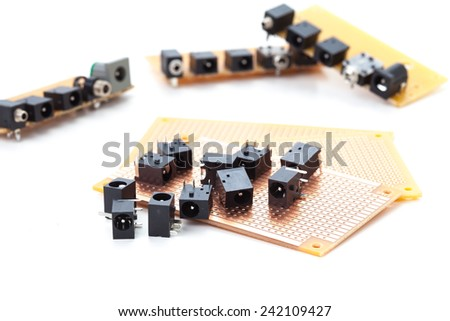 dc power jack and audio jack female placed on the pcb. Electronic printed board. Soldering iron is background - stock photo