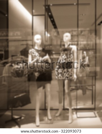 De focused/Blur image of boutique window with dressed mannequins. Boutique display window with mannequins in fashionable dresses. Sepia tone. - stock photo