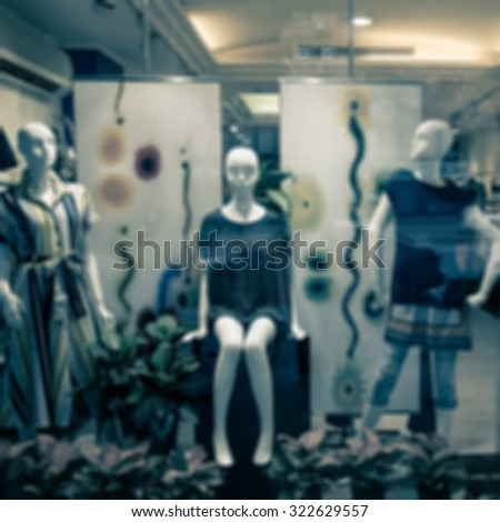 De focused/Blur image of boutique window with dressed mannequins. Boutique display window with mannequins in fashionable dresses. Split tone. - stock photo