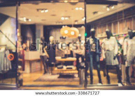 De focused/Blur image of boutique window with dressed mannequins. Boutique display window with mannequins in fashionable dresses. Vintage effect. - stock photo