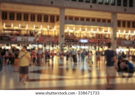 De focused/Blur image of crowd in train station hall. People waiting in line to buy train tickets. Restaurants on second floor. Train station background. Toned image. - stock photo