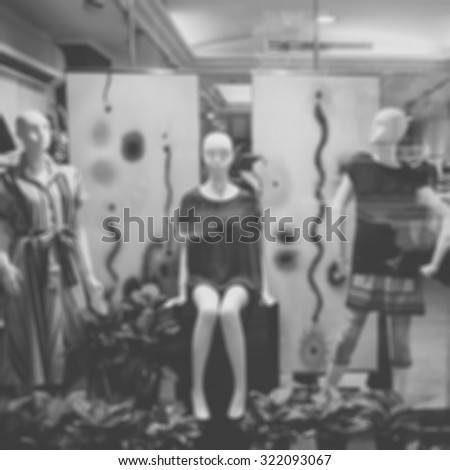 De focused/Blurred, black and white image of boutique window with dressed mannequins. Boutique display window with mannequins in fashionable dresses.  - stock photo