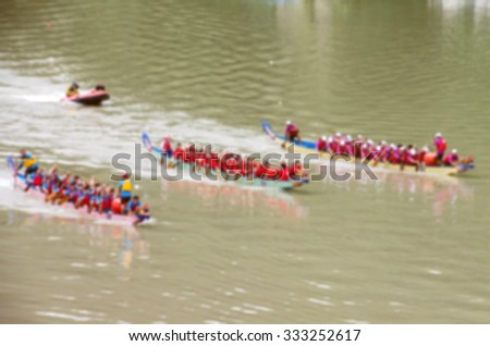 De focused/Blurred image of dragon boat teams at race and followed by a lifeboat.  Toned image. - stock photo