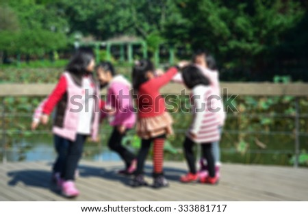 De focused/ Blurred image of young girls playing in the garden in a sunny winter. - stock photo