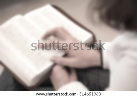 De focused or blurred image of a woman reading the holy bible in the church for religion background - stock photo