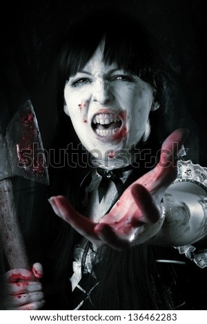 Dead female zombie with bloody axe extends hand to shot. Halloween concept - stock photo