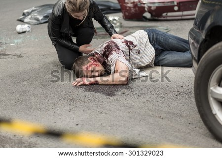 Dead man after car crash and prostrate driver - stock photo