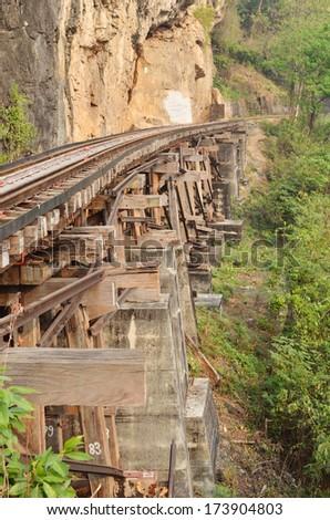Dead railway beside cliff, along Kwai river in Thailand - stock photo