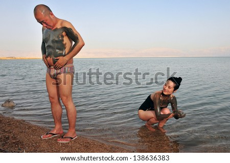 DEAD SEA, ISR - MAY 14:Young Chinese people is enjoys natural mineral mud on May 14 2010.The Dead Sea is filled with minerals including calcium, iodine, saline, potassium, and bromide. - stock photo