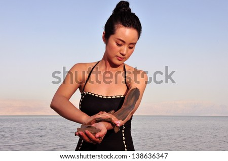 DEAD SEA, ISR - MAY 14:Young Chinese woman  enjoys natural mineral mud on May 14 2010.The Dead Sea is filled with minerals including calcium, iodine, saline, potassium, and bromide. - stock photo